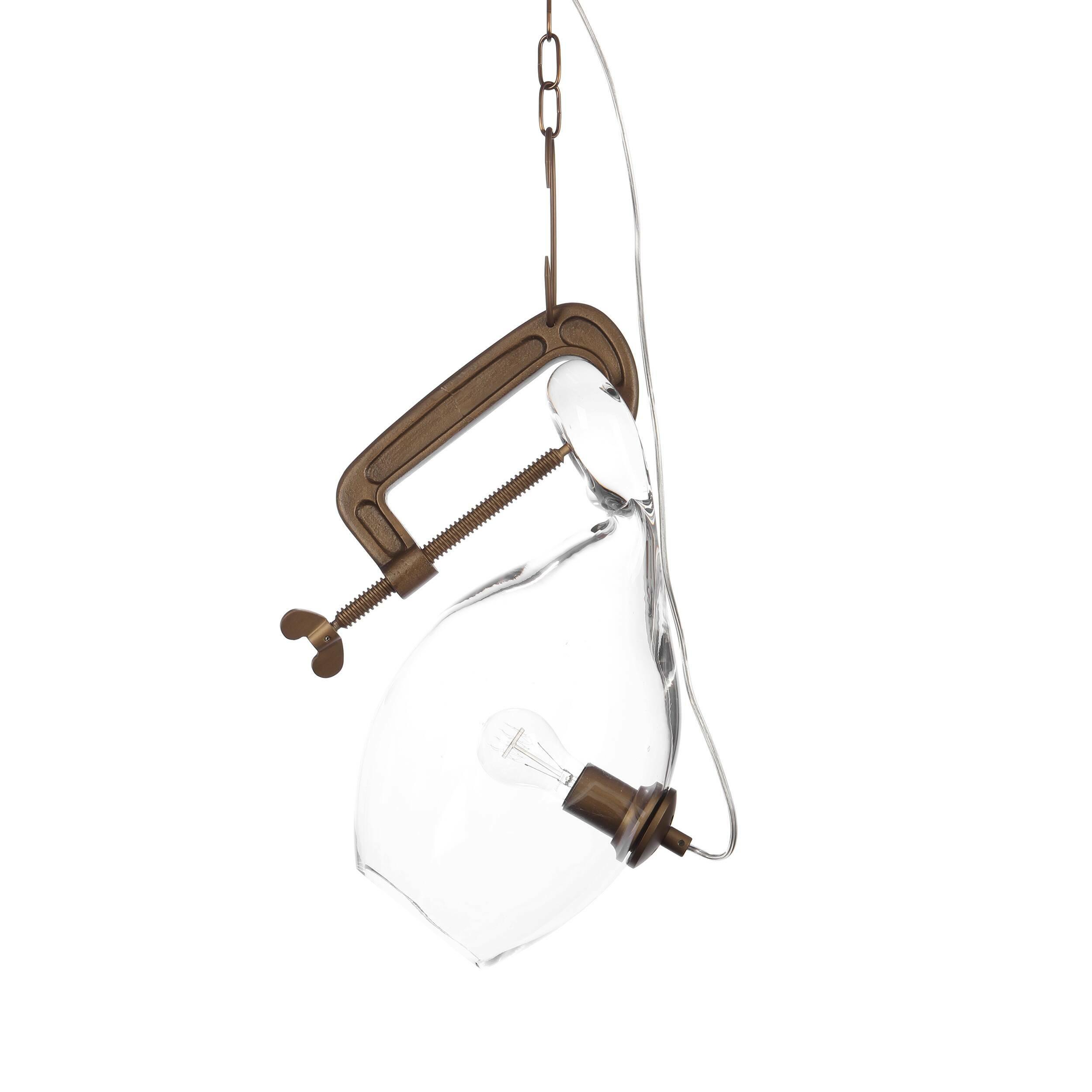 Подвесной светильник ClampПодвесные<br>Подвесной светильник Clamp — это настоящее произведение искусства популярнейшего западного дизайнера Линдси Адельман. Ее светильники имеют характерный почерк и стиль и особенно хорошо гармонируют с общим дизайном современных интерьеров. Светильник имеет весьма необычную и оригинальную форму, которая дополняется изящным декором. На выбор представлены два варианта: белый непрозрачный светильник и прозрачный.<br><br><br><br><br> Абажур светильника изготовлен из прочного стекла. Крепления, держатель и ...<br><br>stock: 25<br>Высота: 48<br>Ширина: 22<br>Длина: 42<br>Количество ламп: 1<br>Материал абажура: Стекло<br>Материал арматуры: Сталь<br>Мощность лампы: 40<br>Ламп в комплекте: Нет<br>Напряжение: 220<br>Тип лампы/цоколь: E27<br>Цвет абажура: Прозрачный<br>Цвет арматуры: Бронза золотая матовая